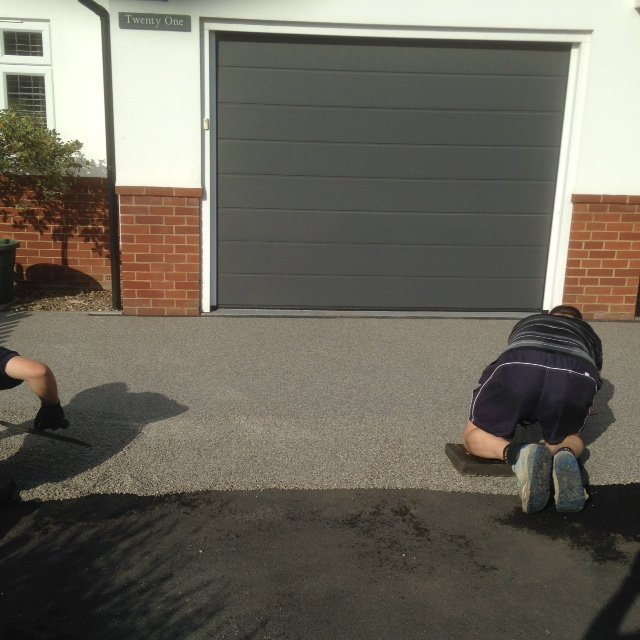 Cork Resin Bound Surfacing Contractors applying resin bound surfacing by hand